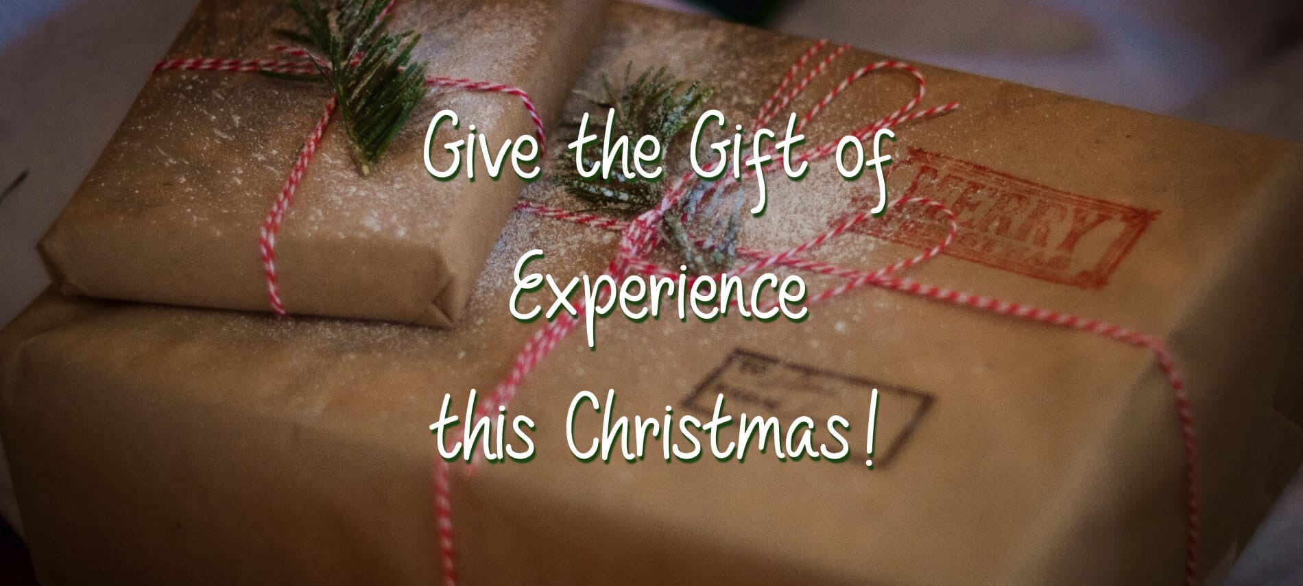 "Two gifts wrapped in brown kraft paper and striped red and white string with the words, ""Give the Gift of Experience this Christmas!"""