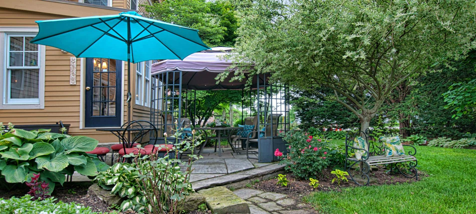 Rear patio with umbrella tables and chairs surrounded by lush green grass, plants and trees