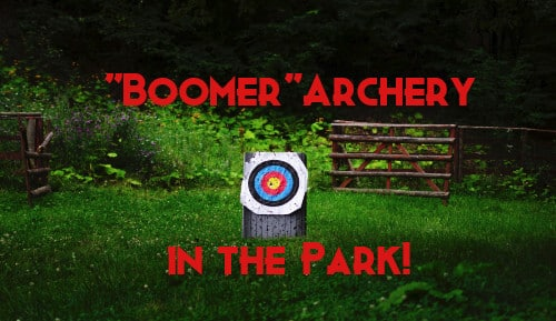 "Archery target set up in a green area with a fence with wording that says ""Boomer Archery in the Park"""