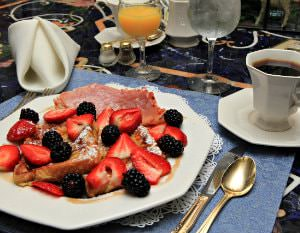 White breakfast plate topped with French toast, fresh strawberries and blackberries, and ham, and orange juice, water and coffee