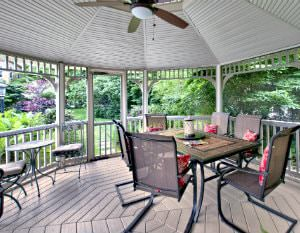 Screened-in gazebo with wood floor, tables and chairs and a ceiling fan surrounded by lush landscaping