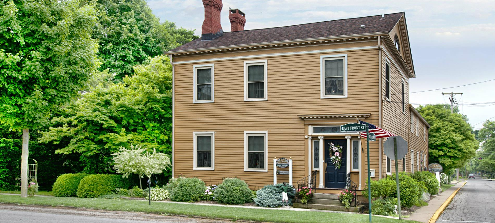 Exterior front view of B&B, tan siding, several windows, two brick chimneys surrounded by lush green trees and shrubs