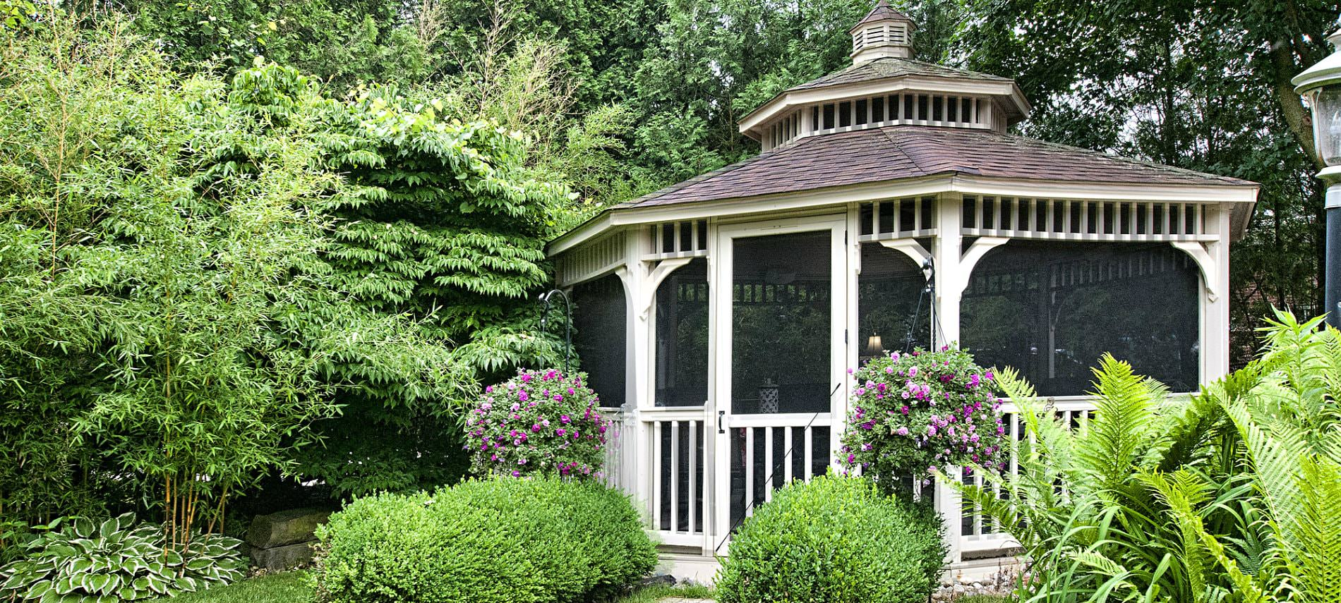 White screened-in gazebo with shingle roof and cupola surrounded by lush green trees and shrubs