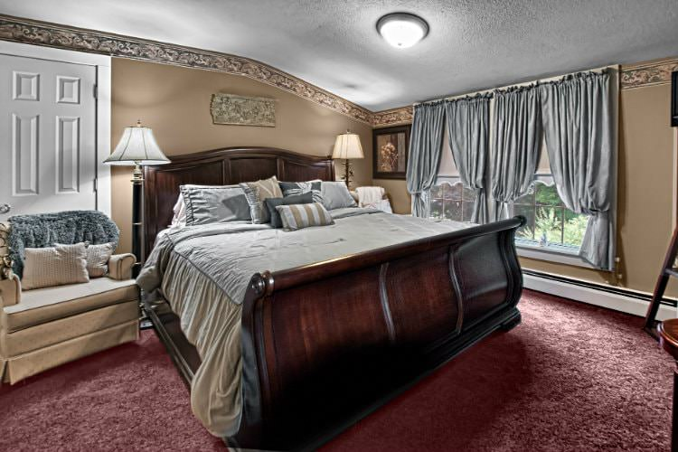 Elegant guest room with tan walls, burgundy carpet, double window, sleigh bed and upholstered chair