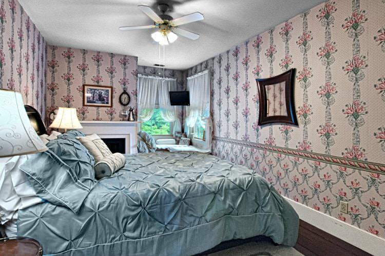 Pretty guest room with floral wallpaper, wood floors, wood bed with light blue shiny comforter, corner windows and fireplace