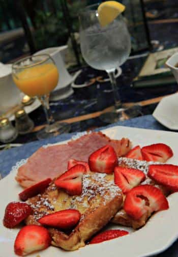 White breakfast plate topped with French toast, fresh strawberries, and ham