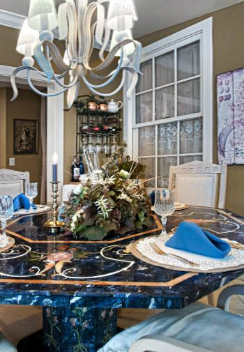 Blue marble octagonal dining table with chairs, chandelier, and centerpiece set for a meal