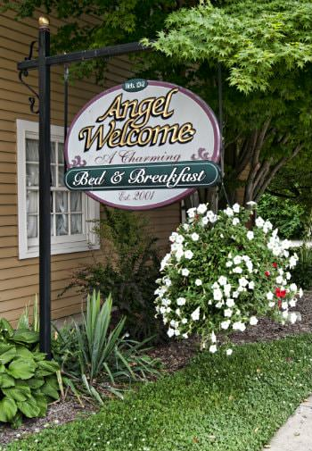 Exterior B&B black sign post with white oval hanging sign that says Angel Welcome A charming B&B established 2001