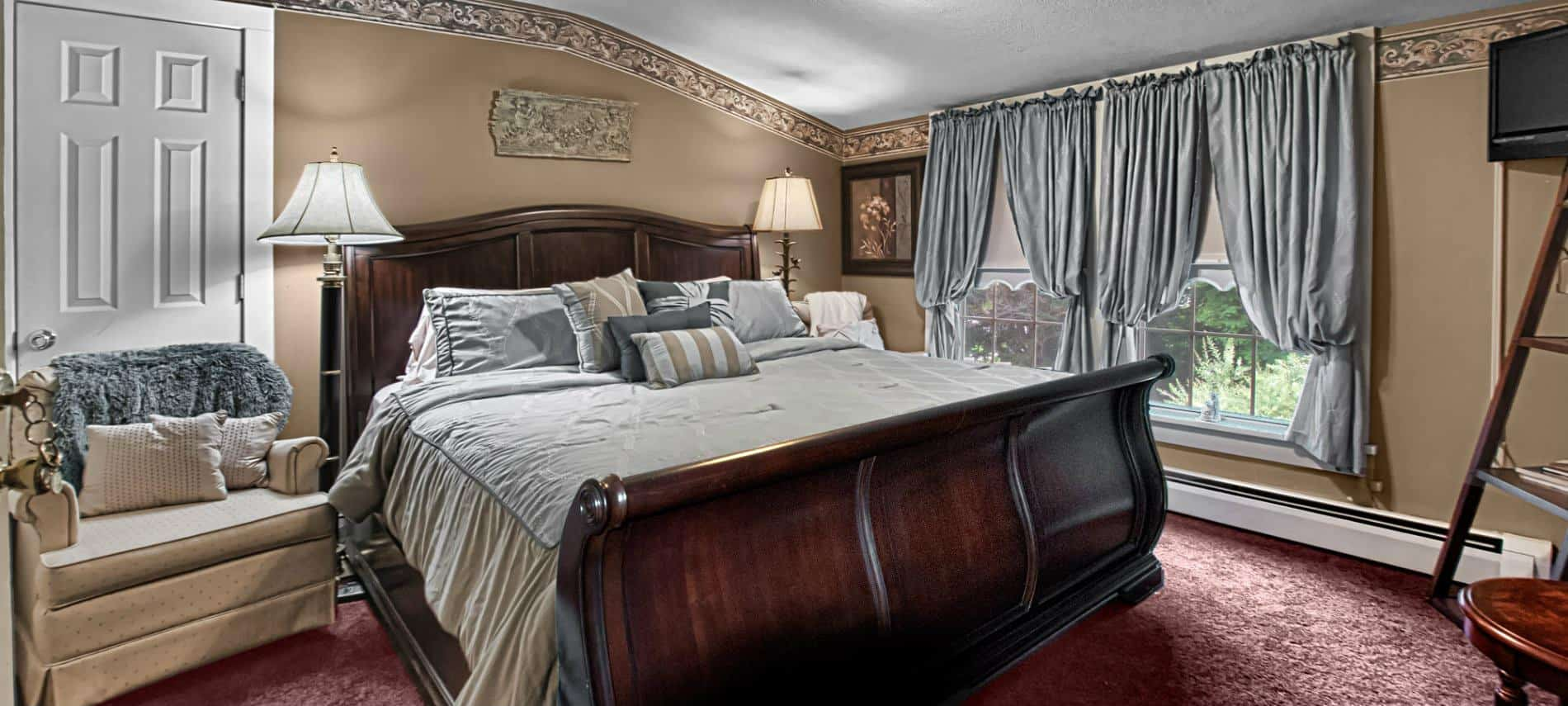 Elegant guest room with tan walls, burgundy carpet, wooden sleigh bed, large window and sitting chairs